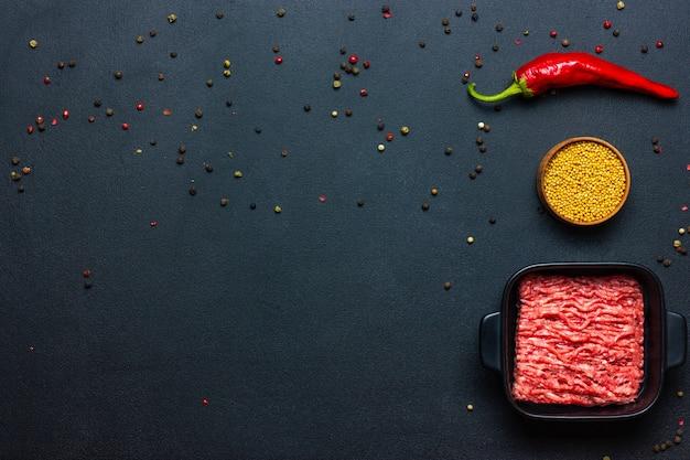 Kulinarischer rahmenhintergrund in dunklen farbtönen mit hackfleisch-pfeffer-gewürzen kirschtomaten paprika ...