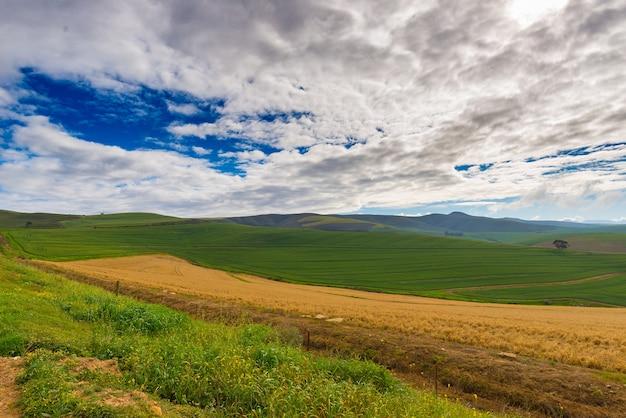 Kultivierte felder und bauernhöfe mit malerischem himmel, landschaftslandwirtschaft