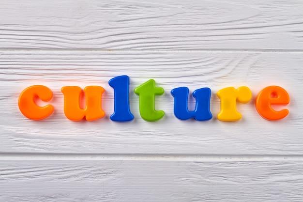 Kultur als nationale leistung. musik, malerei und kunst. bunte buchstaben auf dem holzbrett.