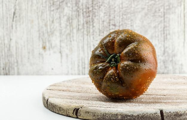 Kumato-tomate auf einem holzstück flach lag auf weißer und schmuddeliger wand