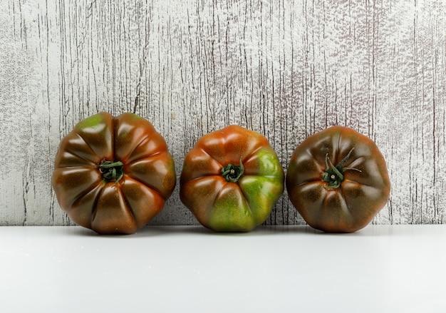 Kumato-tomaten auf weißer und schmuddeliger wand. seitenansicht.