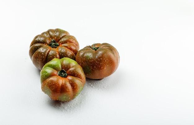 Kumato-tomaten auf weißer wand, hohe winkelansicht.