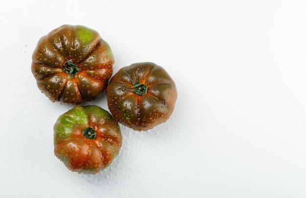 Kumato-tomaten lagen flach auf einer weißen wand