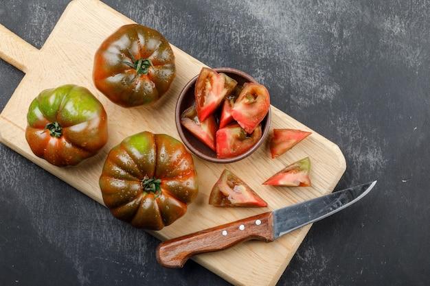 Kumato-tomaten mit messer, scheiben in platte auf schmutz und schneidebrettwand, draufsicht.
