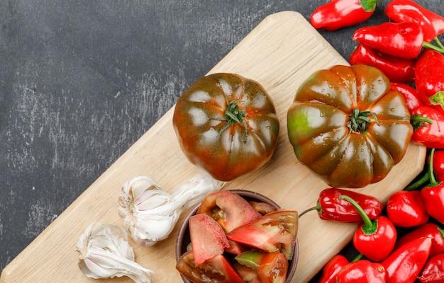 Kumato-tomaten mit scheiben, paprika, knoblauchknollen auf grauer und schneidebrettwand, flach gelegt.