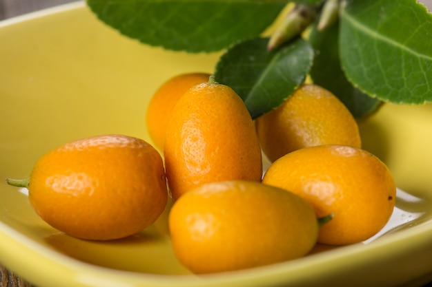 Kumquat auf teller am holztisch