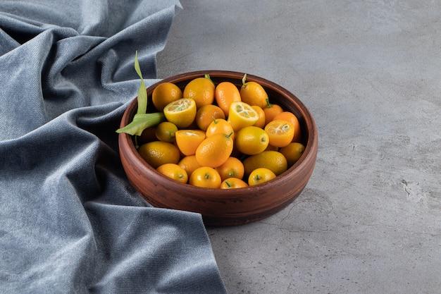 Kumquat früchte in einer schüssel auf einem stück stoff, auf der marmoroberfläche