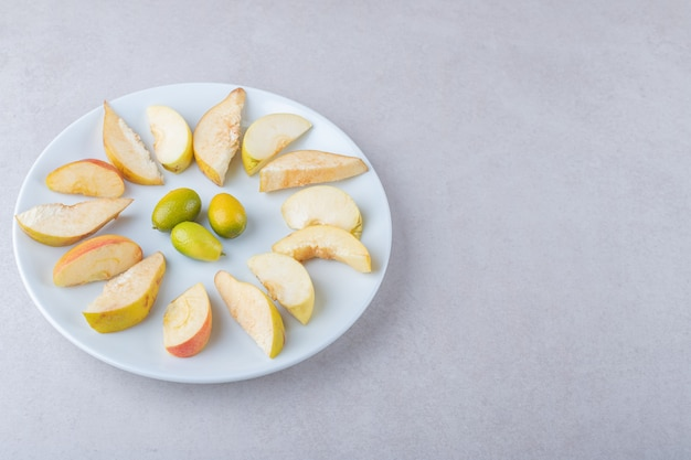 Kumquat und geschnittener apfel auf einem teller auf marmortisch.