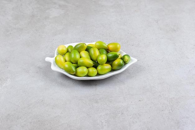 Kumquats stapelten sich auf einer verzierten platte auf marmorhintergrund. hochwertiges foto