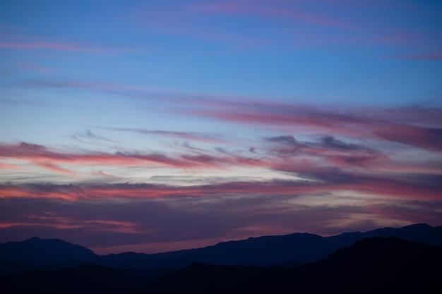Kumulussonnenuntergang bewölkt sich mit der sonne, die auf dunklem hintergrund niederlegt