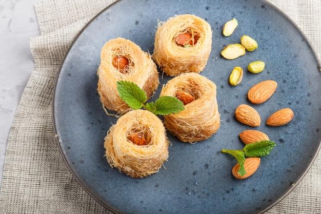 Kunafa, traditionelle arabische bonbons in der blauen keramischen platte auf einem grauen konkreten hintergrund.