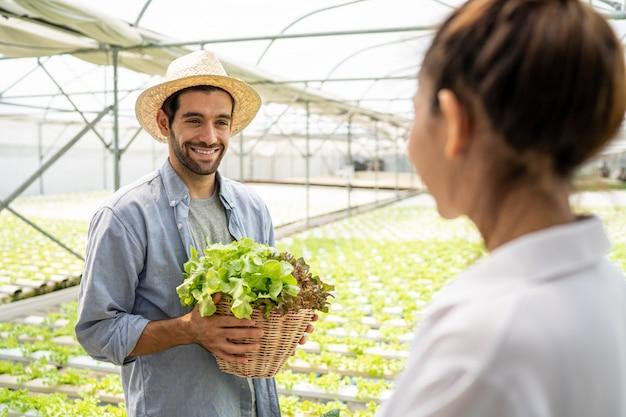 Kunde besucht bio-gemüsefarmen und kauft bio-gemüse mit dem gemüsefarmbesitzer