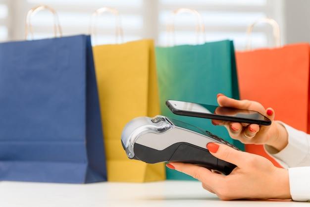 Kunde, der das telefon zur zahlung an den eigentümer im geschäft, restaurant, bargeldlose technologie und kreditkartenzahlungskonzept verwendet