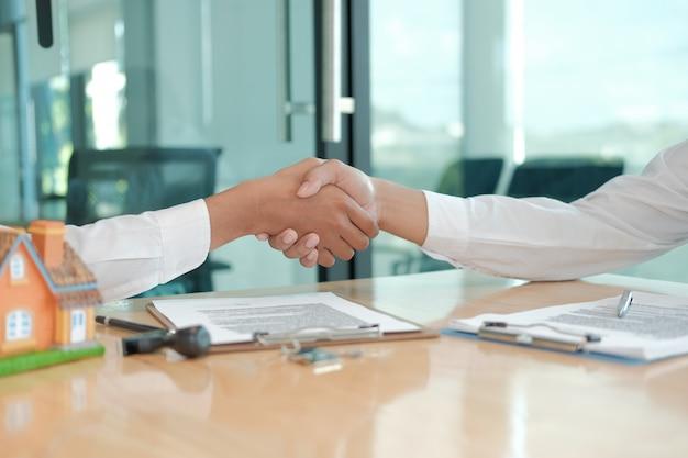 Kunde, der dem grundstücksmaklerhypothekenversicherungsmaklerrechtsanwalt hände rüttelt. kunden-handshake mit finanzberater zur beratung, investment-deal abschließen