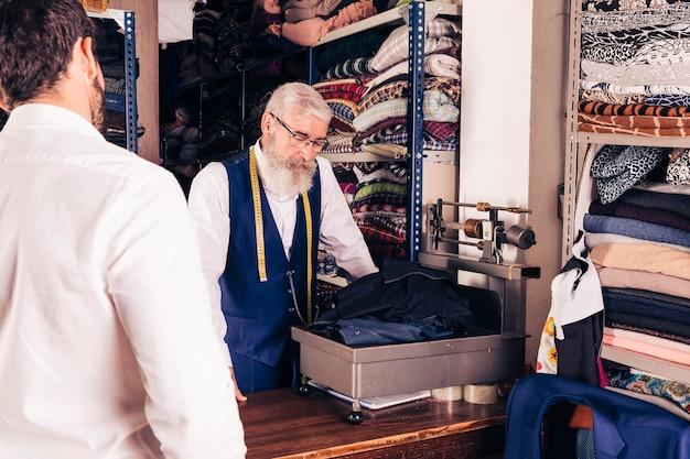 Kunde, der den älteren männlichen schneider wiegt das gewebe im shop betrachtet