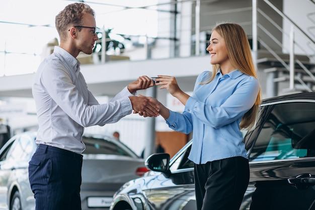 Kunde, der einen kauf in einem autosalon abschließt