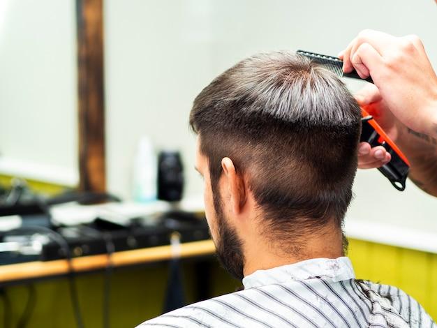 Kunde, der einen neuen haarschnitt von hinten erhält