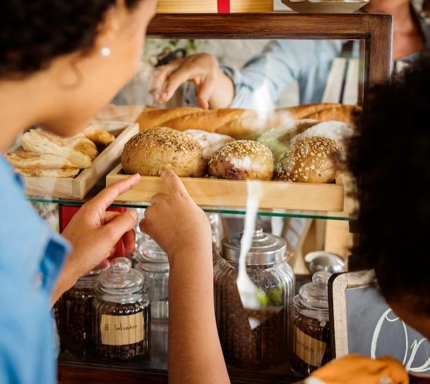 Kunde, der frisches gebackenes brot in der bäckerei kauft