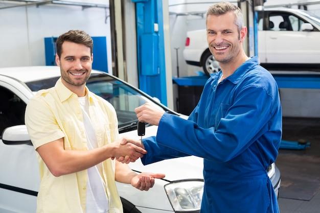 Kunde, der hände mit dem mechaniker nimmt schlüssel rüttelt