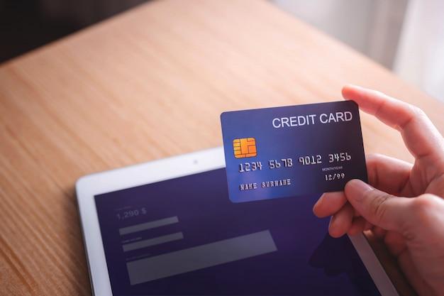 Kunde der jungen frau, der kreditkarte und tablet zur online zahlung verwendet