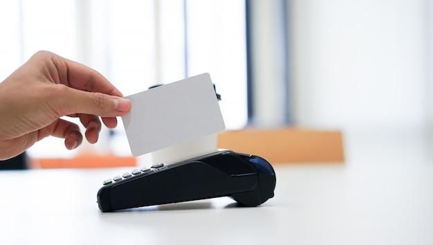 Kunde, der leere kreditkarte verwendet, um auf einem geldautomaten des elektronischen bankwesens zu kaufen