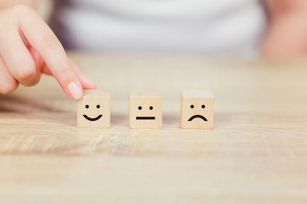 Kunde, der smileygesicht emoticon auf hölzernem würfel bedrängt