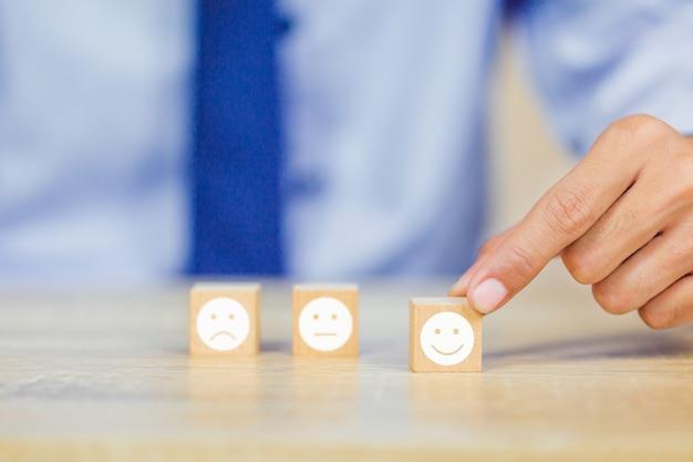 Kunde, der smileygesicht emoticon auf hölzernem würfel drückt