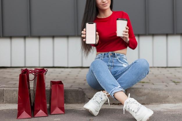 Kunde im roten hemd, das tasse kaffee sitzt und hält