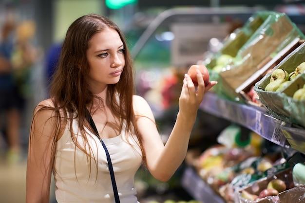 Kunde mit apfel in der hand auf dem marktplatz