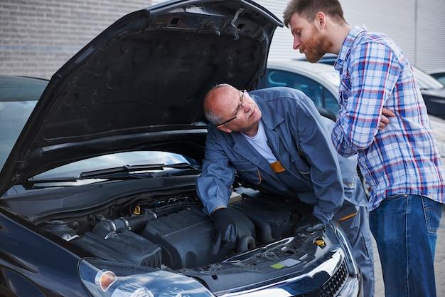Kunde spricht mit einem mechaniker in der werkstatt