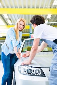 Kunde und autolackierer in der autowerkstatt