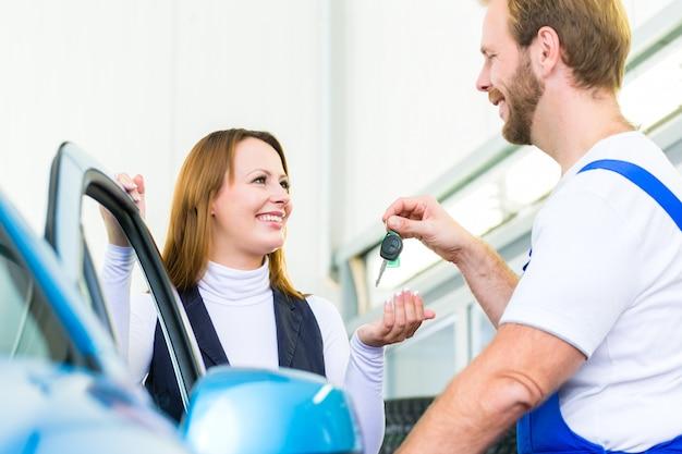 Kunde und kfz-mechaniker in der autowerkstatt
