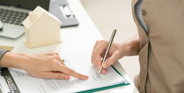 Kunde unterzeichnet dokument, um haus und immobilien zu kaufen