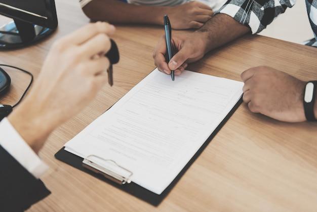 Kunde unterzeichnet vertrag, der schlüssel vom händler empfängt.