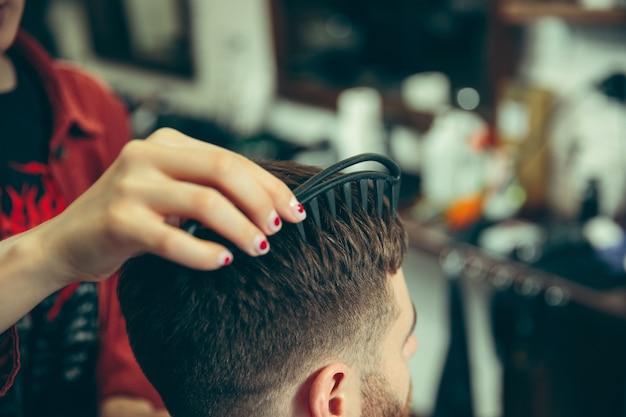 Kunde während der bartrasur im friseursalon. friseurin im salon. geschlechtergleichheit. frau im männerberuf. hände schließen