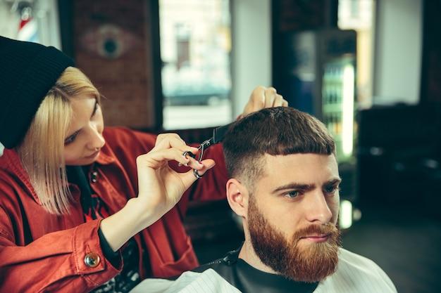 Kunde während der bartrasur im friseursalon. friseurin im salon. geschlechtergleichheit. frau im männerberuf.