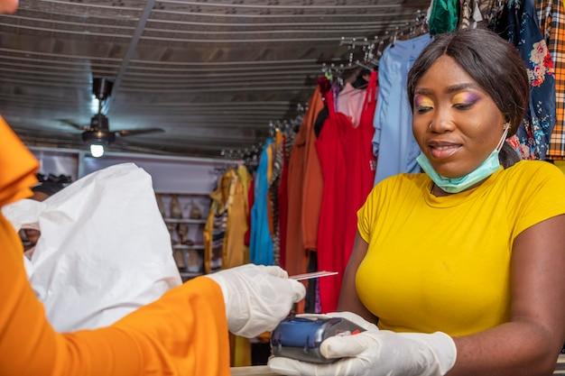 Kunde zahlt mit ihrer kreditkarte, kontaktloses bezahlen mit einem pos-automaten