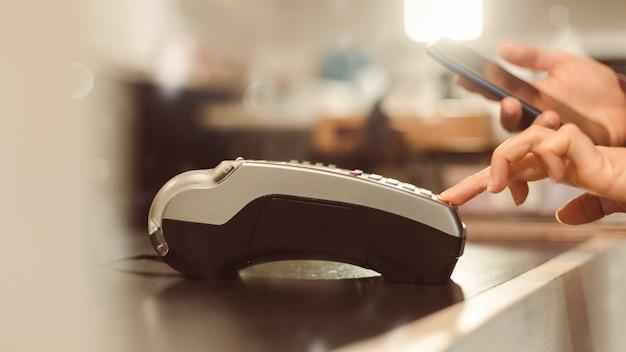 Kunde zahlt mit smartphone im laden mit nfc-technologie