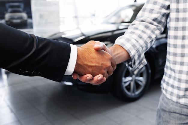 Kunden, die dem professionellen autohändler im autohaus die hand geben