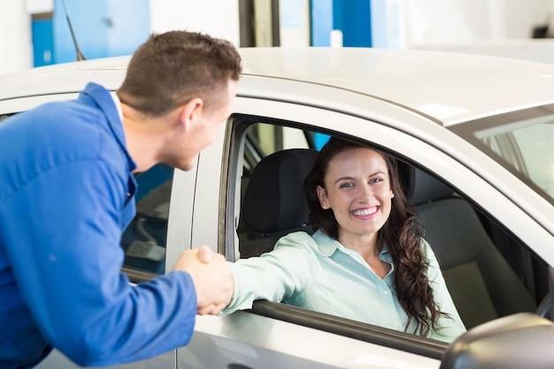 Kunden, die hände mit mechaniker rütteln