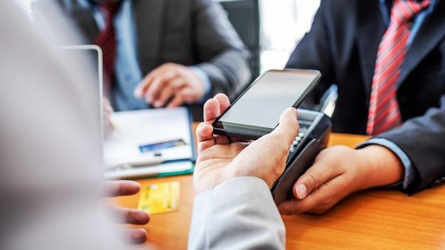 Kunden, die mit der nfc-zahlungstechnologie mit der mobilen app auf dem smartphone die rechnung bezahlen.