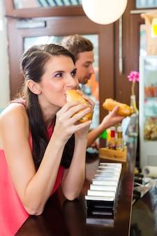 Kunden, die würstchen in der schnellimbiss-snackbar essen