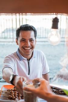 Kunden lächeln, wenn sie ein getränkeglas von einem verkäufer in einem wagenstand erhalten