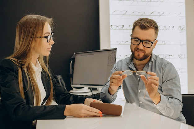 Kunden suchen brillen im optikgeschäft mit hilfe des verkäufers