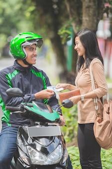 Kunden zahlen für ihre fahrt zum motorradtaxifahrer