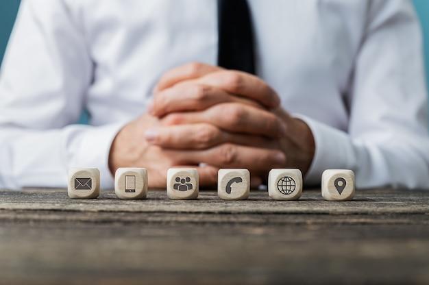 Kundendienst- und hilfekonzept - unternehmer, der an einem rustikalen holzschreibtisch mit sechs würfeln mit kontakt- und informationssymbolen in einer reihe sitzt.