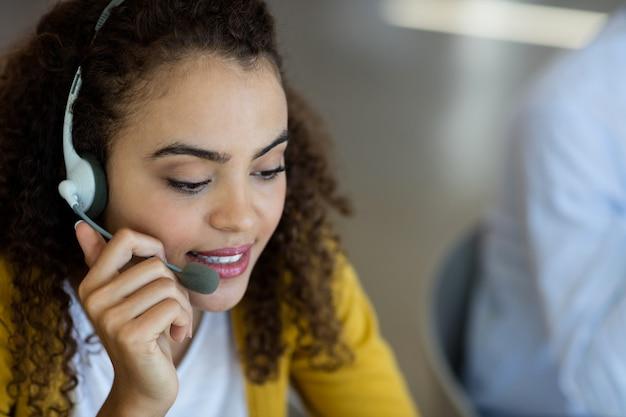 Kundendienstmitarbeiter, der über kopfhörer im büro spricht