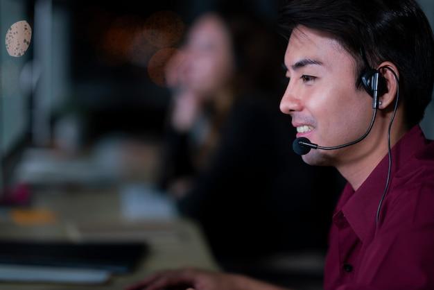 Kundendienstmitarbeiter des thailändischen asiatischen mannes, die nachtschicht im callcenter arbeiten