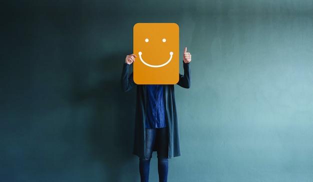 Kundenerfahrungen oder menschliches emotionales konzept über daumen hoch und ein glückliches gesicht