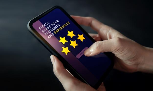 Kundenerlebnis-konzept. frau, die handy benutzt, um feedback über das internet zu geben. positive bewertung mit fünf sternen. umfragen zur kundenzufriedenheit